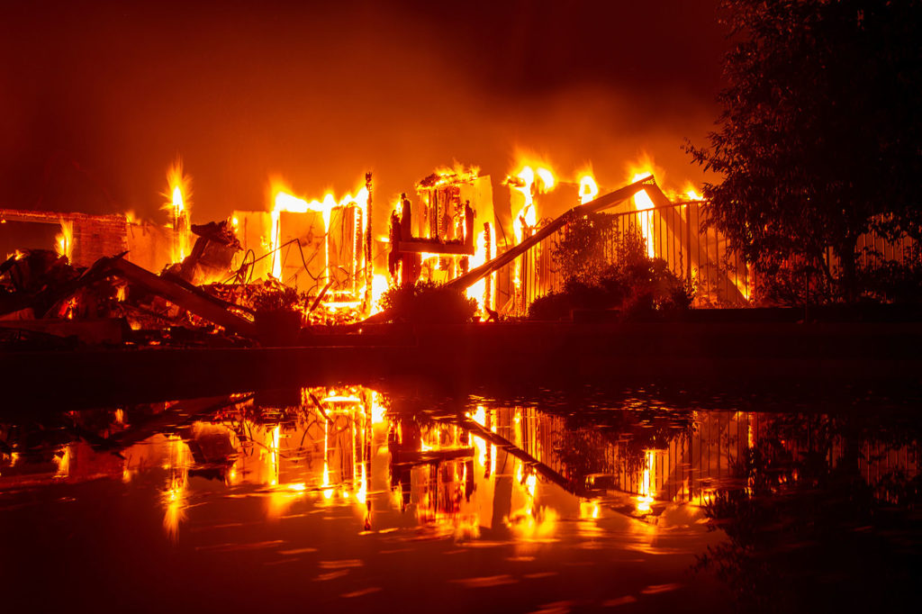 Lángoló otthon tükröződik egy medence fizén a Kaliforniai tűzvész során. Fotó: AFP / Josh Edelson