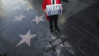 Los Angeles, 2018. július 25.Donald Trump amerikai elnök szétzúzott csillaga mellett áll egy Amerikát nagynak megőrizni jelentésű felirattal egy férfi a hollywoodi Hírességek sétányán, Los Angelesben 2018. július 25-én. A csákánnyal elkövetett vandál támadást hajnalban jelentették be a rendőrségen, és az ügyben egy személyt őrizetbe vettek. A csillagot Trump a The Apprentice című valóságshowban végzett munkájával érdemelte ki. (MTI/AP/Reed Saxon)