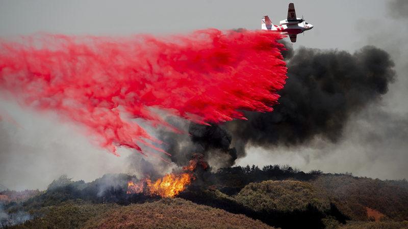 Lakeport, 2018. július 31.Gyulladásgátló vegyszert szórnak repülőgépről tűzoltók a kaliforniai Lakeportban 2018. július 30-án. Kaliforniában pusztító két erdőtűz miatt legalább nyolc ember – köztük négy tűzoltó – életét vesztette, hetet eltűntnek nyilvánítottak és 38 ezren otthonuk elhagyására kényszerültek. (MTI/AP/Noah Berger)