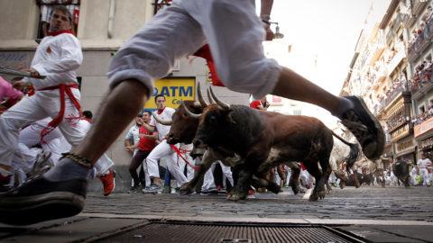 Pamplona, 2018. július 9.Bikák elől menekülnek résztvevők a pamplonai San Fermín fesztivál harmadik napján, 2018. július 9-én. A spanyol város védőszentjének tiszteletére 1591 óta évente megrendezett kilencnapos fiesta egyik fő attrakciója a reggelenkénti bikafuttatás, amelynek során férfiak százai teszik próbára bátorságukat azzal, hogy az arénába hajtott állatok előtt végigszaladnak Pamplona utcáin. (MTI/EPA/Villar López)