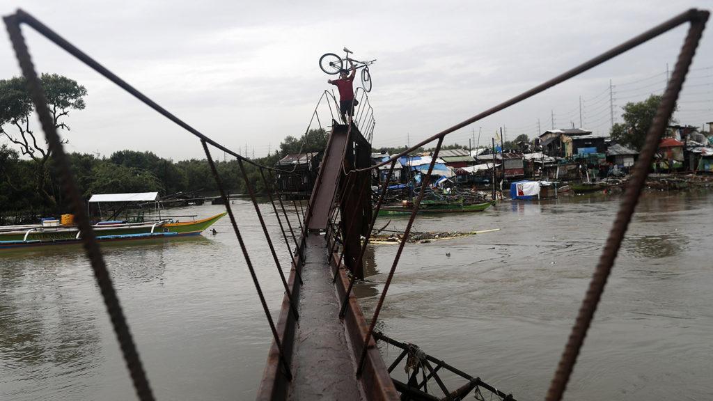 Las Pinas, 2018. július 18.Fülöp-szigeteki férfi viszi kerékpárját egy árvízzel elárasztott utcán a Manilától délre fekvő Las Pinasban 2018. július 18-án, miután a Henry nevű alacsony légnyomású áramlat hatására kialakult hatalmas esőzések áradásokat okoztak az országban. (MTI/EPA/Francis R. Malasig)