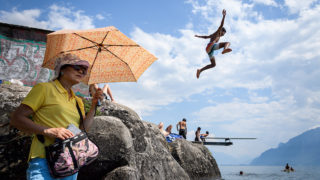 A boy jumps into Geneva Lake in Saint Saphorin, western Switzerland, above a tourist protecting herself from the sun with an umbrella as a heatwave is sweeping across northern Europe on July 31, 2018. / AFP PHOTO / Fabrice COFFRINI