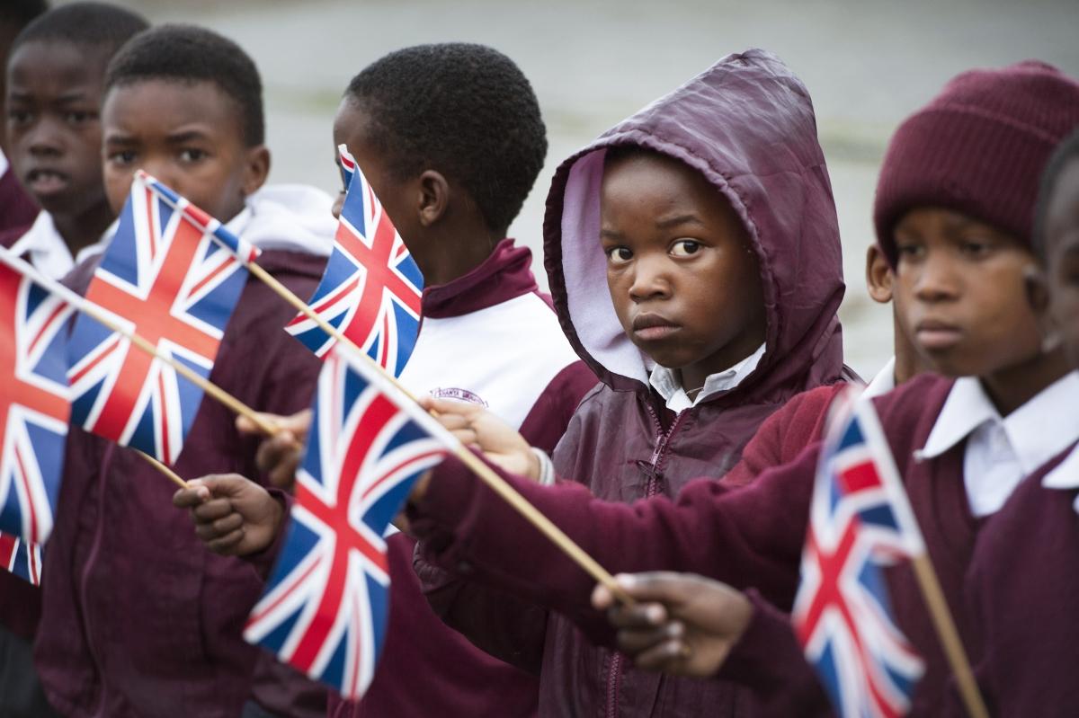 Iskolásgyerekek várnak brit zászlóval a kezükben Theresa May brit kormányfő érkezésére a fokvárosi ID Mkhize középiskolában 2018. augusztus 28-án. Theresa May afrikai körútja során Nigériába és Kenyába is ellátogat Rodger BOSCH