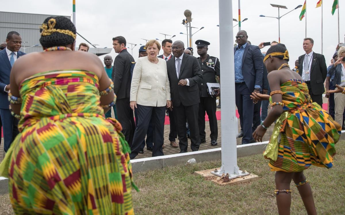 Angela Merkel német kancellár az őt köszöntő ghánai táncosok előadását nézi az Accra-Kotaka repülőtéren 2018. augusztus 30-án. Merkel háromnapos afrikai körútja során látogatott Ghánába. (MTI/EPA/Felipe Trueba)Photo: Michael Kappeler/dpa