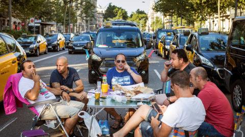 Barcelona, 2018. augusztus 1.Sztrájkoló taxisofőrök lezárnak egy utcát Barcelonában 2018. augusztus 1-jén. A taxisok több spanyol városban is beszüntették a munkát azt követelve, hogy a hatóságok ne adjanak ki a törvényi előírásnál több működési engedélyt az olyan alternatív személyszállító cégeknek mint az Uber és a Cabify. (MTI/EPA/Enric Fontcuberta)