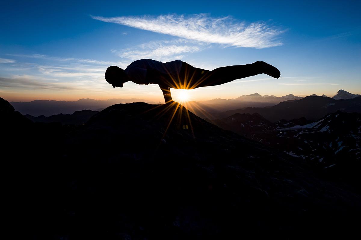 Verbier, 2018. augusztus 2.Emilien Badoux svájci hegyikerékpáros és jógaoktató jógázik napkeltekor a Mont Fort-csúcson, tengerszint feletti 3329 méteres magasságon, a svájci Nendaz és Verbier között 2018. augusztus 2-án. (MTI/EPA/Jean-Christophe Bott)