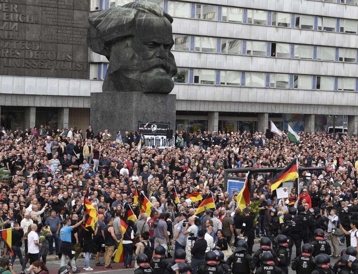 """Chemnitz, 2018. augusztus 27. Szélsõjobboldali tüntetõk tiltakoznak a kelet-németországi Chemnitzben két nappal ezelõtt történt gyilkosság miatt Karl Marx német filozófus-közgazdásznak, a kommunista eszmék egyik kidolgozójának szobra elõtt 2018. augusztus 27-én. A chemnitzi rendõrség és az ügyészség korábban arról tájékoztatott, hogy a belvárosban tartott szabadtéri fesztivál szombati programjai után, éjjel összetûzésbe keveredett egy csoport """"különbözõ nemzetiségû férfi"""". Egy ember életét vesztette, ketten súlyos sebesüléseket szenvedtek. Az emberöléssel egy 23 éves szíriai és egy 22 éves iraki állampolgárt gyanúsítanak.  (MTI/EPA/Filip Singer)"""