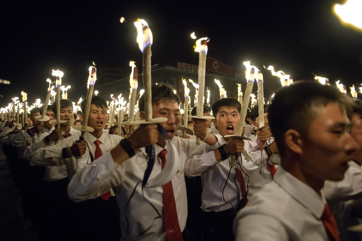 Észak-koreai diákok énekelnek egy fáklyás felvonuláson az ország alapításának 70. évfordulója alkalmából tartott ünnepségsorozaton Phenjanban 2018. szeptember 10-én / AFP PHOTO / Ed JONES
