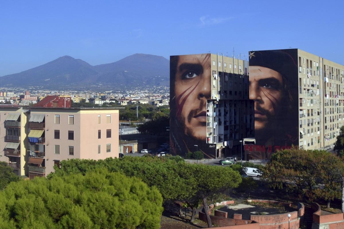 """Nápoly, 2018. szeptember 24. Ernesto """"Che"""" Guevara argentin származású latin-amerikai gerillaparancsnokot ábrázoló kétrészes falfestmény egy nápolyi társasház falain 2018. szeptember 23-án. Jorit Agoch olasz mûvész alkotása egyenként 300 négyzetméter területû, elkészítéséhez negyven napra volt szükség. (MTI/AP/Jorit Agoch)"""