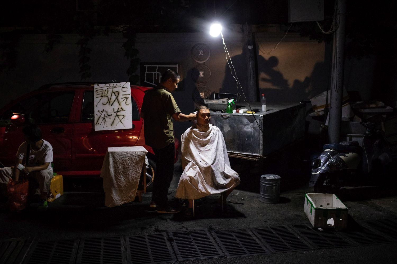 Peking, 2018. szeptember 5. A 2018. augusztus 22-i képen egy férfi haját vágják egy szegénynegyed utcáján, Peking Csaojang nevû üzleti negyedének szomszédságában. A szegénynegyed viskóiban mintegy ezer, zömében vidékrõl feltelepült kínai munkás él. Az elmúlt években Pekingben a vidéki munkavállalók szállásai közül sokat elbontottak a városrendezés szellemében, a fõváros elhagyására kényszerítve a fedél nélkül maradt embereket. Li Ko-csiang miniszterelnök kormánya 2018 és 2020 között országosan 15 millió, nyomornegyedben épült otthon felszámolását ütemezte elõ. A vezetés a pekingi lakosság növekedésének felsõ határát 2020-ra 23 millió fõben szabja meg a 2016 és 2035 közötti két évtizedet felölelõ fejlesztési terv szerint, amelyet a Kínai Kommunista Párt Központi Bizottsága és az Államtanács által 2017. szeptember 29-én hagyott jóvá. A kínai fõvárosban élõ, bejelentett lakcímmel rendelkezõk száma 2016 végén 21,73 millióra rúgott. (MTI/EPA/Roman Pilipej)