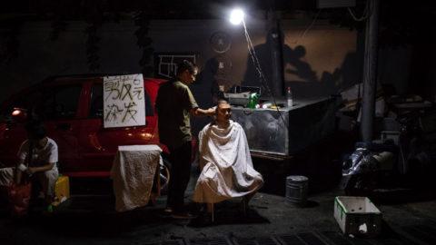 Peking, 2018. szeptember 5.A 2018. augusztus 22-i képen egy férfi haját vágják egy szegénynegyed utcáján, Peking Csaojang nevű üzleti negyedének szomszédságában. A szegénynegyed viskóiban mintegy ezer, zömében vidékről feltelepült kínai munkás él. Az elmúlt években Pekingben a vidéki munkavállalók szállásai közül sokat elbontottak a városrendezés szellemében, a főváros elhagyására kényszerítve a fedél nélkül maradt embereket. Li Ko-csiang miniszterelnök kormánya 2018 és 2020 között országosan 15 millió, nyomornegyedben épült otthon felszámolását ütemezte elő. A vezetés a pekingi lakosság növekedésének felső határát 2020-ra 23 millió főben szabja meg a 2016 és 2035 közötti két évtizedet felölelő fejlesztési terv szerint, amelyet a Kínai Kommunista Párt Központi Bizottsága és az Államtanács által 2017. szeptember 29-én hagyott jóvá. A kínai fővárosban élő, bejelentett lakcímmel rendelkezők száma 2016 végén 21,73 millióra rúgott. (MTI/EPA/Roman Pilipej)