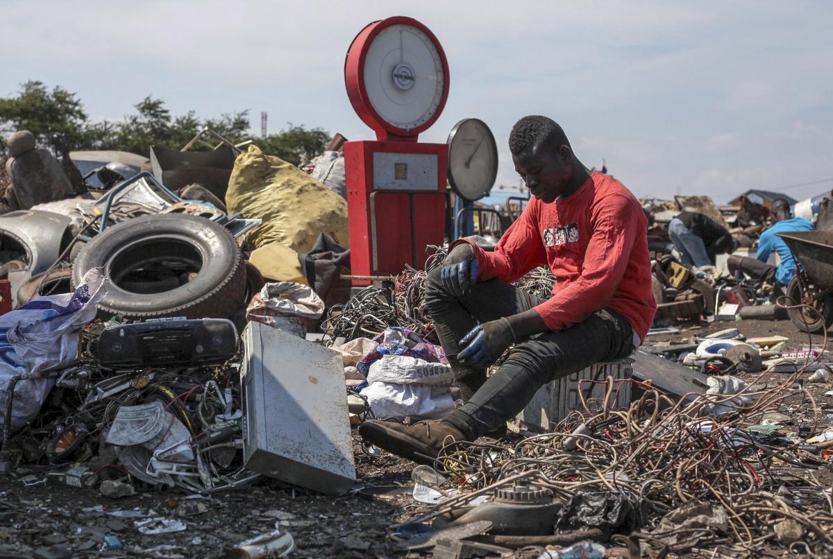 Accra, 2018. szeptembert 6. A 2018. augusztus 27-i képen hulladékot válogat egy ghánai férfi egy elektronikaihulladék-lerakó telepen a fõváros, Accra Agbogbloshie néven ismert kereskedelmi negyedében. Az Old Fadama nyomornegyed közelében mûködõ lerakó emberek százainak megélhetését biztosítja, akik a leselejtezett cikkekbõl kiszerelik az újrahasznosítható alkatrészeket, majd az értékesíthetõ fémeket égetéssel nyerik ki a burkolatból. A vörösrézkábeleket és a használt alkatrészekbõl összeszerelt vagy felújított mûszaki cikkeket illegálisan, kéz alatt adják el. Az elektronikus hulladékok égetése a levegõ, a talaj és a vizek súlyos szennyezésével jár, mert az e-hulladék ólmot, higanyt, kadmiumot és egyéb nehézfémeket, valamint arzént és számos mérgezõ vegyi anyagot tartalmaz. A Greenpeace nemzetközi környezetvédõ szervezet által az Agbogbloshie területén gyûjtött víz- és talajminták a jelen levõ káros anyagok százszorosát mutatták ki a megengedett értékekhez képest. A Bázeli Egyezmény tiltja a gazdaságilag fejlett államokban keletkezett veszélyes hulladékok lerakását a fejlõdõ országokban, engedélyezi azonban a mûszaki cikkek javítás és újrahasznosítás céljából történõ exportját. Ghánában, Nigériában és egyéb afrikai államokban a helyi technológiai fejlettség mértékét jóval meghaladó mennyiségben van jelen elektronikai hulladék, ami a nemzetközi jogszabályok kijátszására utal. (MTI/EPA/Christian Thompson)