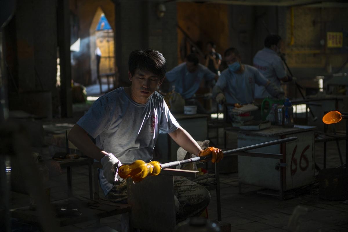 Cepo, 2018. szeptember 12. A 2018. szeptember 9-i képen munkadarabokat formáznak egy hagyományos üvegfúvó mûhely dolgozói a kelet-kínai Santung tartománybeli Cepóban (Zibo). A Santung Lingsang, a világ legnagyobb, dísztárgyakat és ékszereket készítõ kézi üvegfúvó üzeme 460 embert foglalkoztat. A termékeit az Egyesült Államokba, Németországba, Franciaországba, Olaszországba és közel-keleti államokba, valamint környezõ ázsiai országokba exportálják évente több mint 5 millió dollár értékben. Az alapanyagot 1400 Celsius-fokon lágyítják meg az üzem 1,6 méter magas és 3,5 méter mély olvasztókemencéjében, majd az üvegolvadékot fúvással, nyújtással, hengerléssel, vágással, préseléssel és egyéb formázási technikákkal munkálják meg. (MTI/EPA/Aleksandar Plavevski)