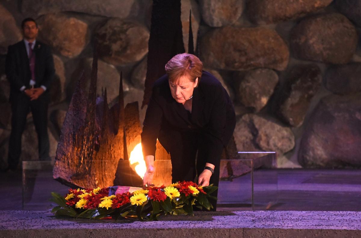 Angela Merkel német kancellár felszítja az örök lángot az Emlékezés Csarnokában, a jeruzsálemi Jad Vasem Intézet és Emlékmúzeumban 2018. október 4-én. / AFP PHOTO / POOL / DEBBIE HILL