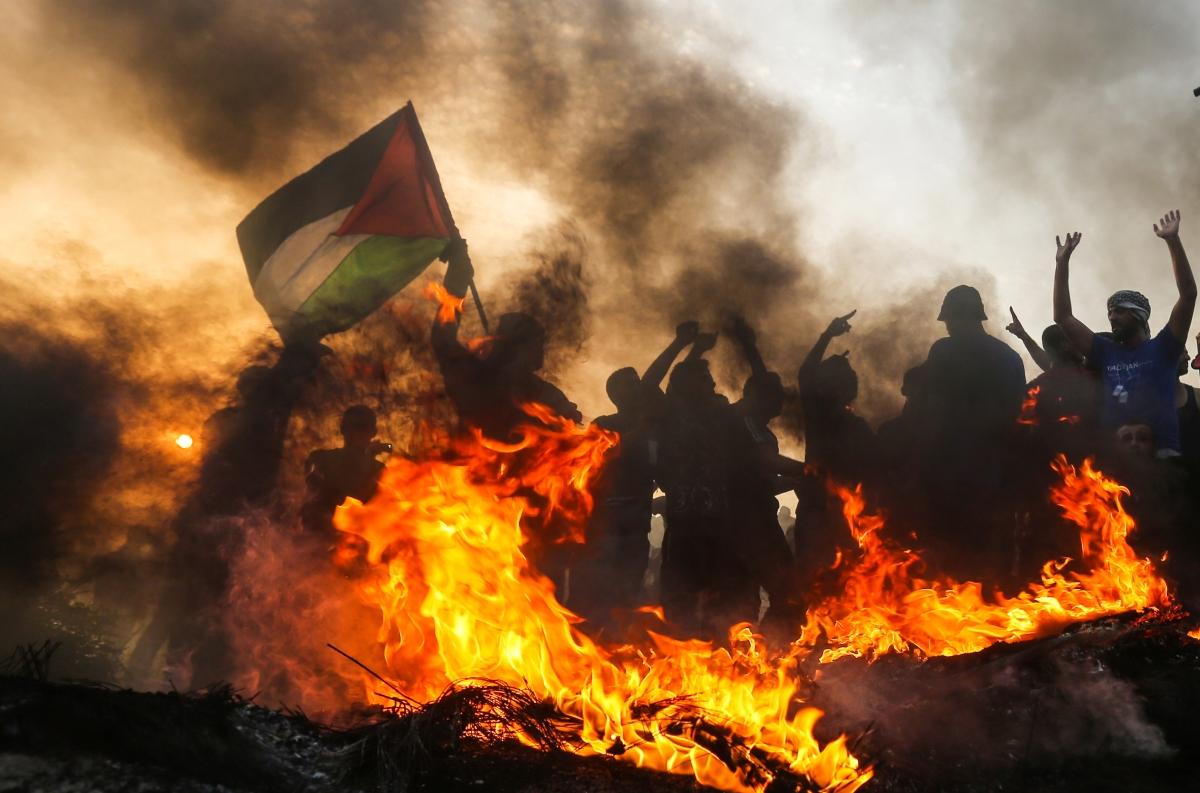 Palesztin tüntetők nemzeti zászlóval a Gázai övezetben közel az izraeli határhozFotó: Mahmud Hams / AFP