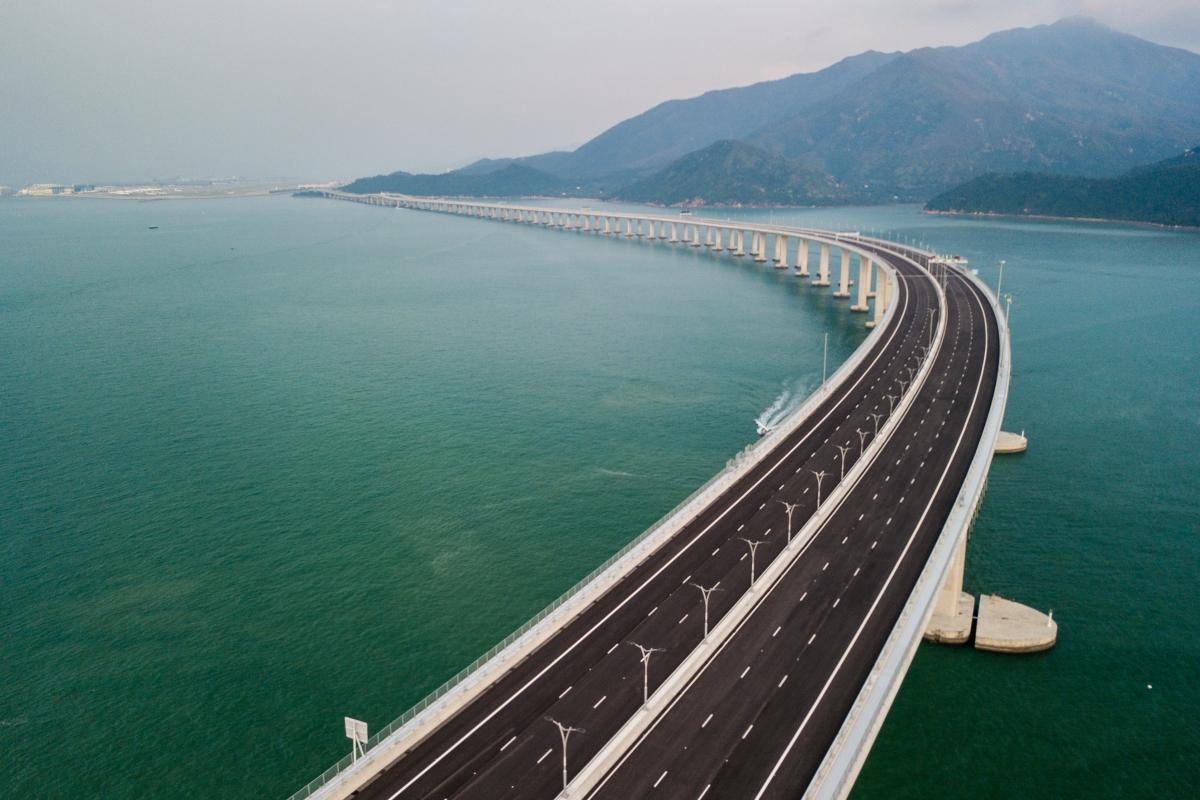 A Hongkong-Csuhaj-Makaó híd, a világ leghosszabb tengeri hídja a dél-kínai Kuangtung tartományban fekvő Csuhajban 2018. október 24-én, amikor megindult rajta a forgalom. A három várost a Gyöngy-folyó torkolatvidékén összekötő híd teljes hossza 55 kilométer, ebből a főhíd 23 kilométer, az alagút 6,7 kilométer, és két mesterséges sziget is része a létesítménynek. (Photo by Anthony WALLACE / AFP)