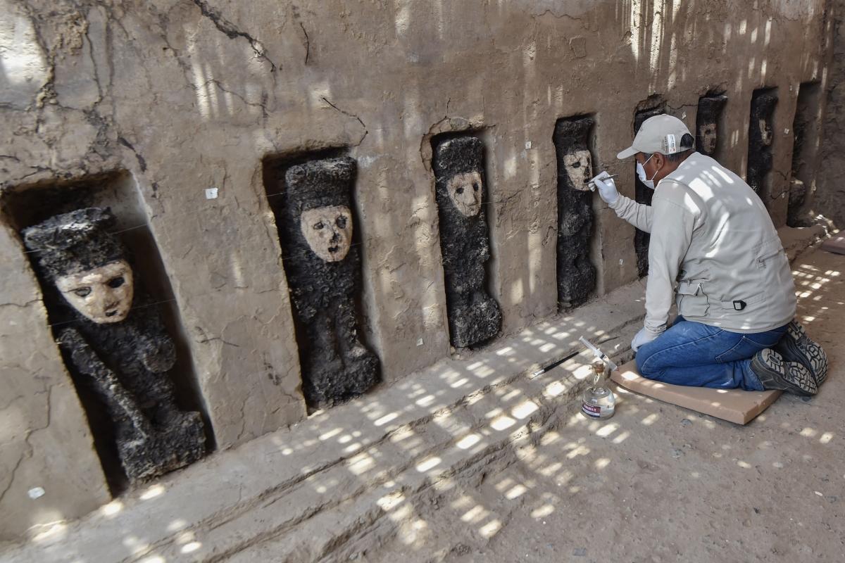 aszobrok agyagmaszkját tisztják le a perui Trujillo közelében lévő prekolumbián vályogvárosban, Chan Chanban 2018. október 22-én. A fából faragott bálványok az inka birodalmat megelőző chimú kultúrában épített város egyik szakrális központjának bejáratát védték. A perui kulturális minisztérium október 22-én mutatta be a faszobrokat egy sor fontos régészeti lelet részeként.(Photo by CRIS BOURONCLE / AFP)