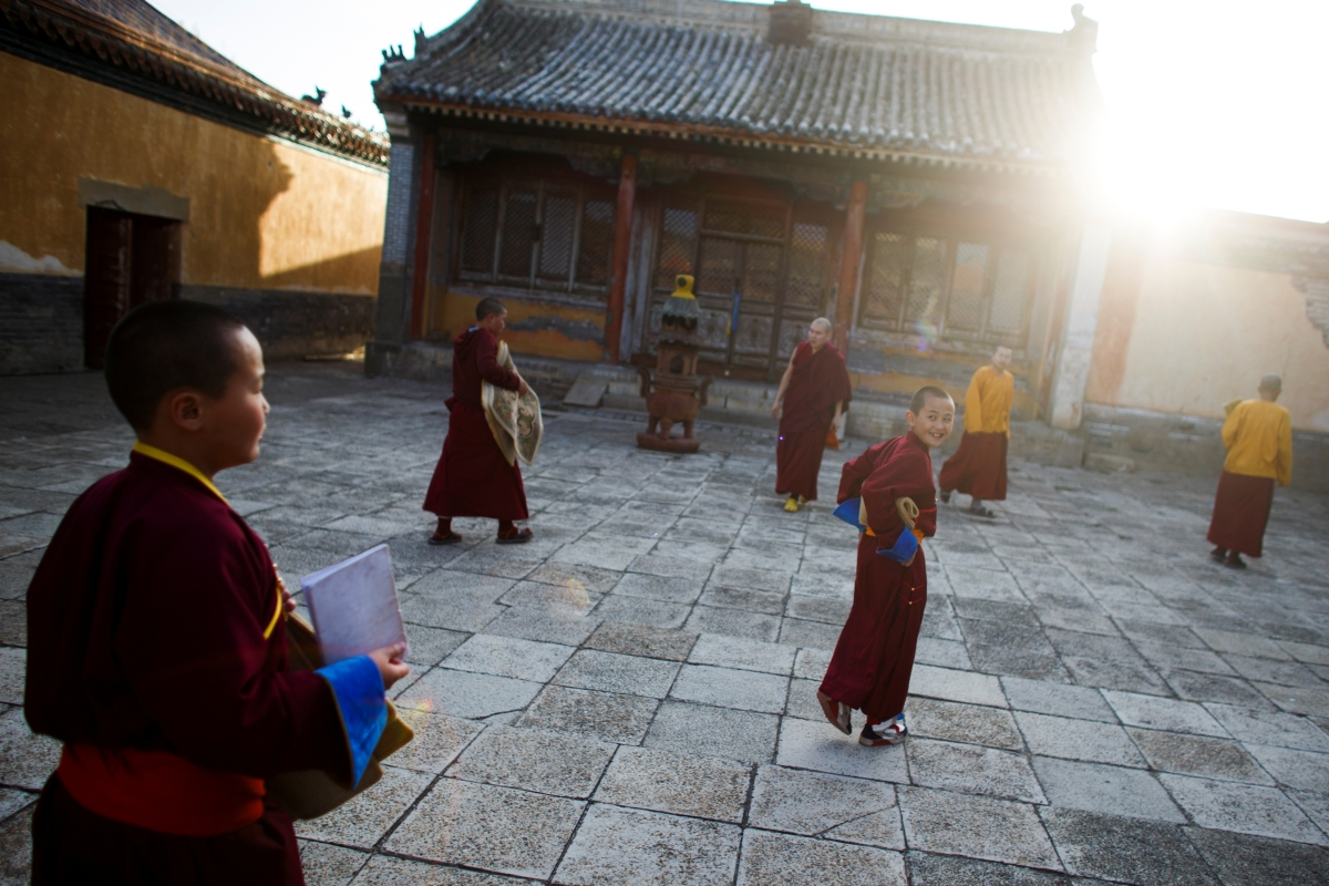"""Young Buddhist monks arrive for an evening prayer recital session in the courtyard of the Amarbayasgalant Monastery in the Baruunburen district, Selenge province, Mongolia, April 26, 2018. REUTERS/Thomas Peter  SEARCH """"MILLENNIAL MONKS"""" FOR THIS STORY. SEARCH """"WIDER IMAGE"""" FOR ALL STORIES. TPX IMAGES OF THE DAY."""