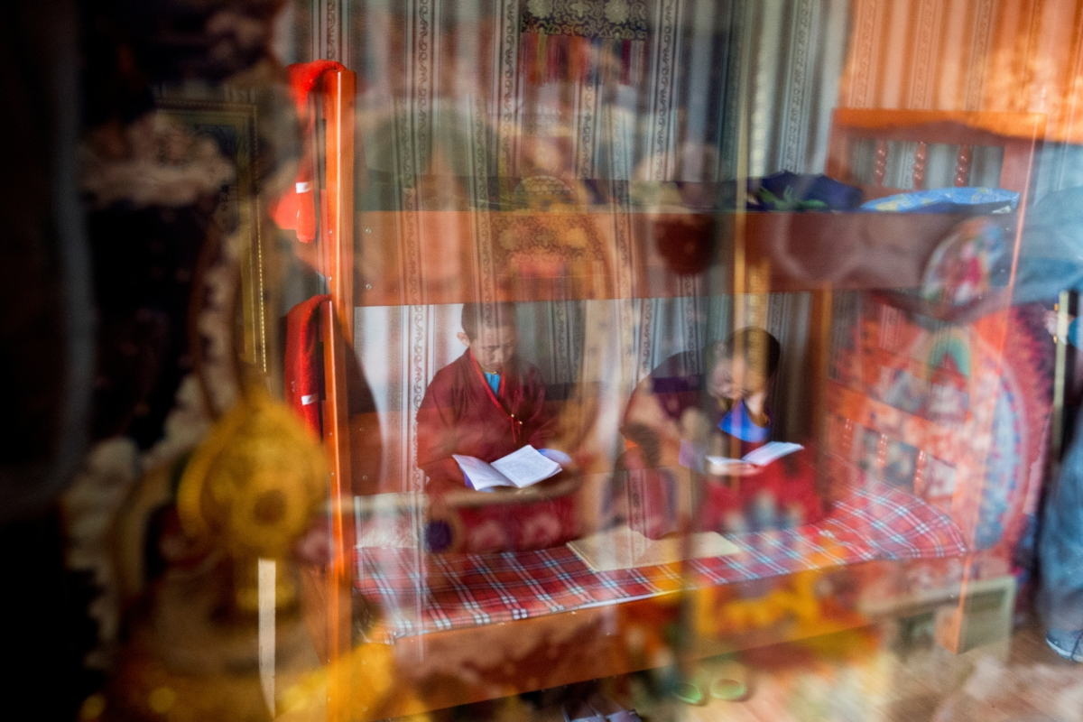 """Young Buddhist monks Temuulen and Batkhan Tuul are reflected in a glass cabinet as they study religious texts shortly after waking up in their room at the Amarbayasgalant Monastery in the Baruunburen district, Selenge province, Mongolia, April 26, 2018. REUTERS/Thomas Peter   SEARCH """"MILLENNIAL MONKS"""" FOR THIS STORY. SEARCH """"WIDER IMAGE"""" FOR ALL STORIES."""