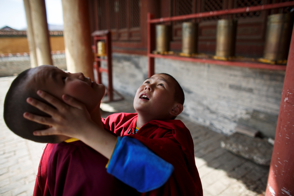 """Young Buddhist monks Temuulen and Batkhan Tuul look at birds nesting under the roof of the main temple of the Amarbayasgalant Monastery in the Baruunburen district, Selenge province, Mongolia, April 26, 2018. REUTERS/Thomas Peter  SEARCH """"MILLENNIAL MONKS"""" FOR THIS STORY. SEARCH """"WIDER IMAGE"""" FOR ALL STORIES."""