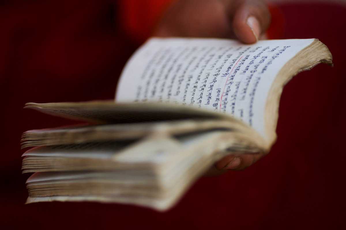 """A young Buddhist monk reads a prayer book during a recital session at the Amarbayasgalant Monastery in the Baruunburen district, Selenge province, Mongolia, April 26, 2018. REUTERS/Thomas Peter  SEARCH """"MILLENNIAL MONKS"""" FOR THIS STORY. SEARCH """"WIDER IMAGE"""" FOR ALL STORIES."""