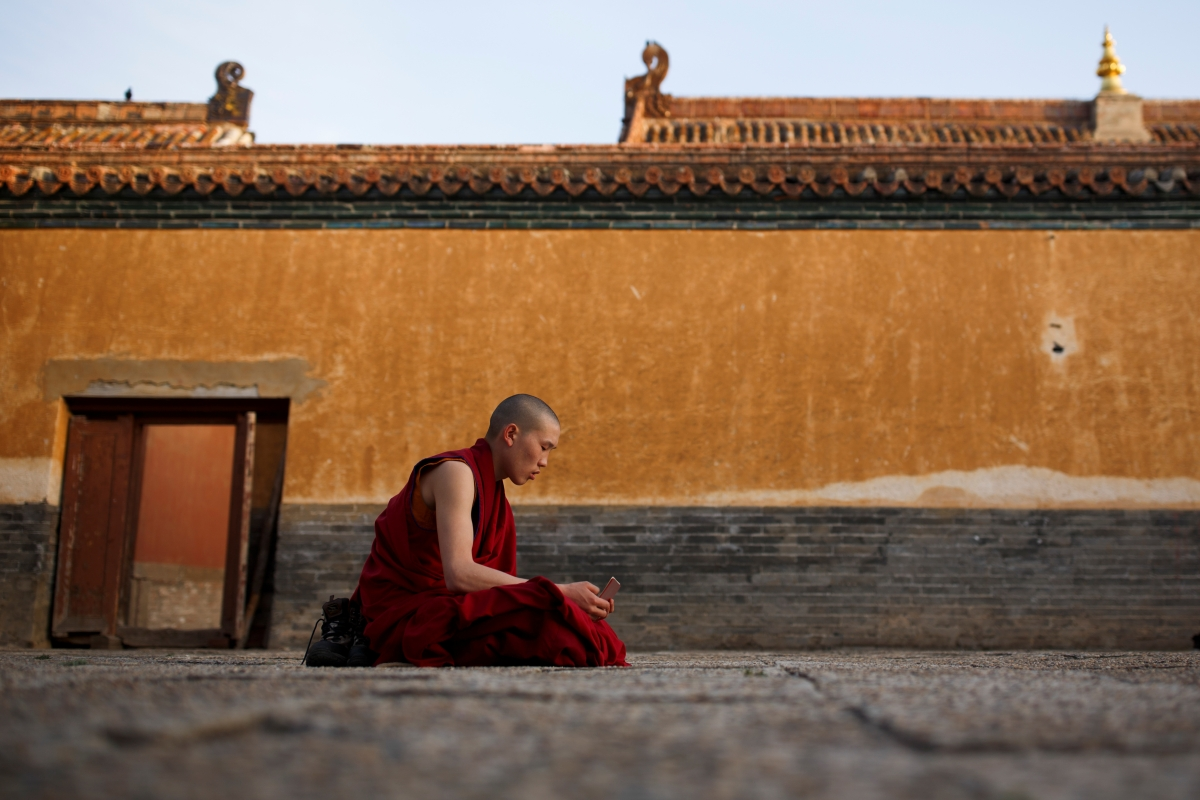 """A young Buddhist monk recites prayers in a courtyard of the Amarbayasgalant Monastery in the Baruunburen district, Selenge province, Mongolia, April 26, 2018. REUTERS/Thomas Peter  SEARCH """"MILLENNIAL MONKS"""" FOR THIS STORY. SEARCH """"WIDER IMAGE"""" FOR ALL STORIES."""
