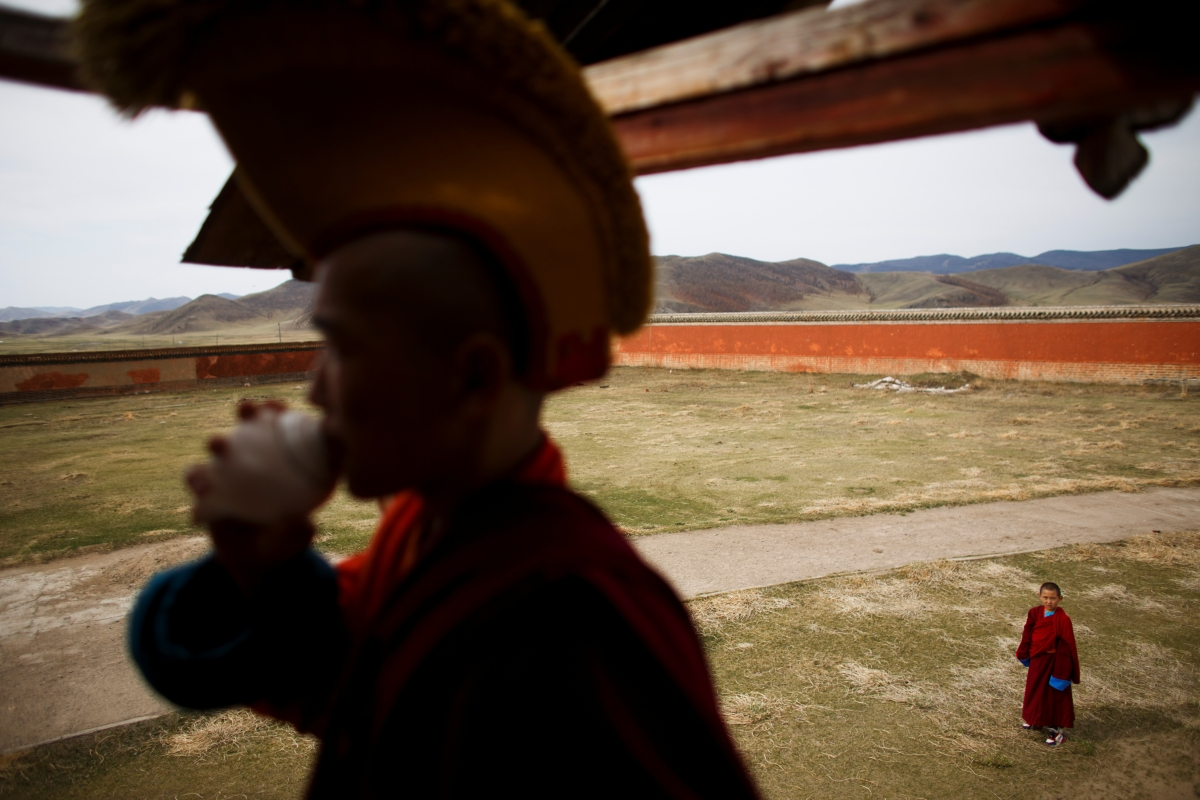 """Young Buddhist monk Temuulen watches a fellow monk blow a seashell as a call for prayers at Amarbayasgalant Monastery in the Baruunburen district, Selenge province, Mongolia, April 26, 2018. REUTERS/Thomas Peter  SEARCH """"MILLENNIAL MONKS"""" FOR THIS STORY. SEARCH """"WIDER IMAGE"""" FOR ALL STORIES."""
