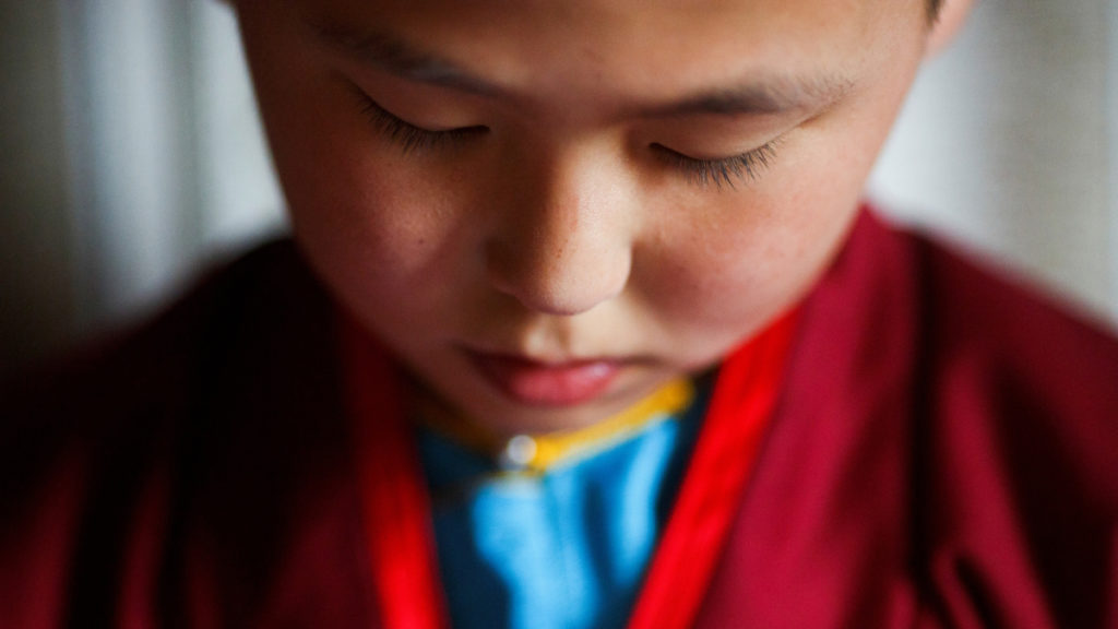 """Young Buddhist monk Temuulen studies religious texts shortly after waking up in his room at the Amarbayasgalant Monastery in the Baruunburen district, Selenge province, Mongolia, April 26, 2018. REUTERS/Thomas Peter  SEARCH """"MILLENNIAL MONKS"""" FOR THIS STORY. SEARCH """"WIDER IMAGE"""" FOR ALL STORIES. TPX IMAGES OF THE DAY."""
