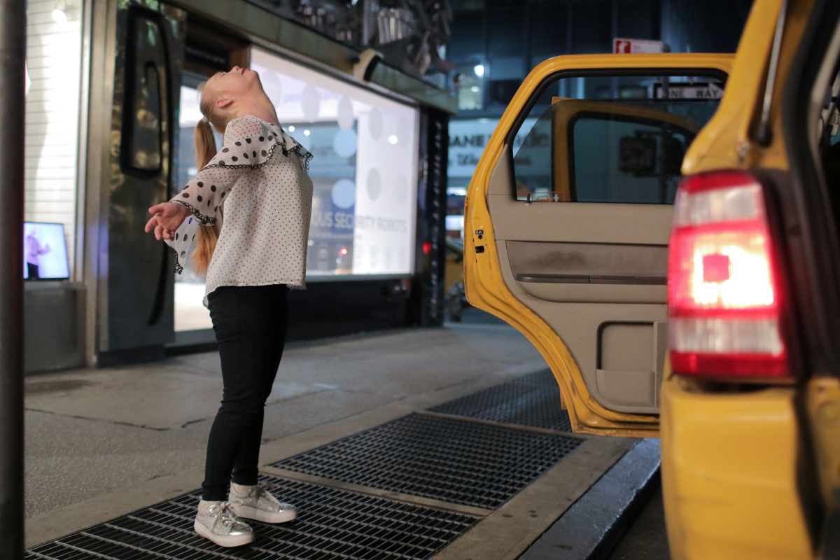 """Model Madeline Stuart, who has Down's syndrome, celebrates after stepping out of a taxi cab as she arrives for New York Fashion Week in New York City, U.S., September 5, 2018. REUTERS/Andrew Kelly  SEARCH """"MODEL MADELINE"""" FOR THIS STORY. SEARCH """"WIDER IMAGE"""" FOR ALL STORIES.  THE IMAGES SHOULD ONLY BE USED TOGETHER WITH THE STORY - NO STAND-ALONE USES"""