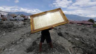 Palu, 2018. október 8.Bekeretezett képet visz egy férfi házak romjai mellett az indonéziai Celebeszen (Sulawesi) fekvő Paluban 2018. október 8-án. A szeptember 28-án történt 7,7-es erősségű földrengésnek és az azt követő szökőárnak a legfrissebb összesítések szerint legkevesebb 1944 halottja és ezernél is több sérültje van. A földrengésben megsemmisült házak számát mintegy 66 ezerre becsülik. (MTI/EPA/Hotli Simanjuntak)