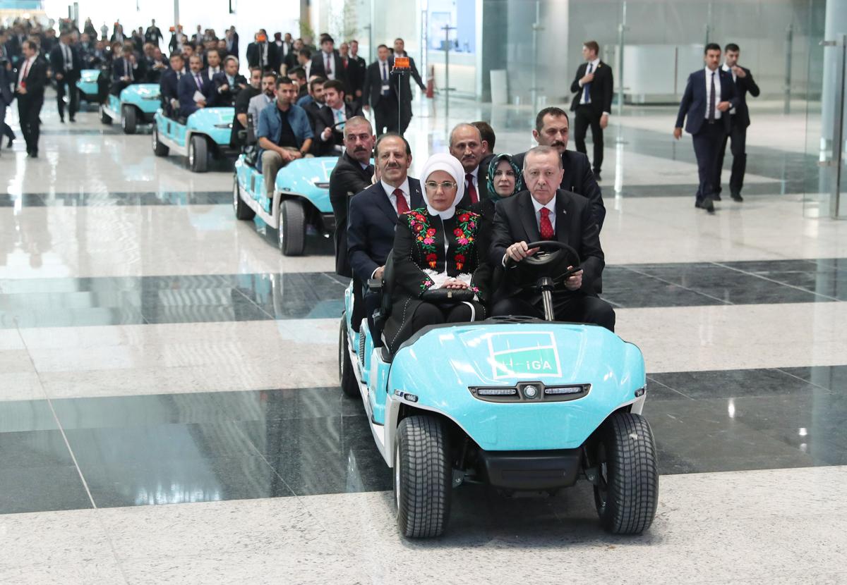 A török elnöki sajtóiroda felvételén Recep Tayyip Erdogan török elnök reptéri járművet vezet a felesége, Emine Erdogan mellett az isztambuli új repülőtér átadóünnepségén, a török köztársaság kikiáltásának 95. évfordulóján. Az egyelőre név nélküli nemzetközi légikikötő Isztambul európai oldalán, Arnavutköy városrészben épült meg a nagyváros harmadik repterekéntFotó: Török Elnöki Hivatal / AFP