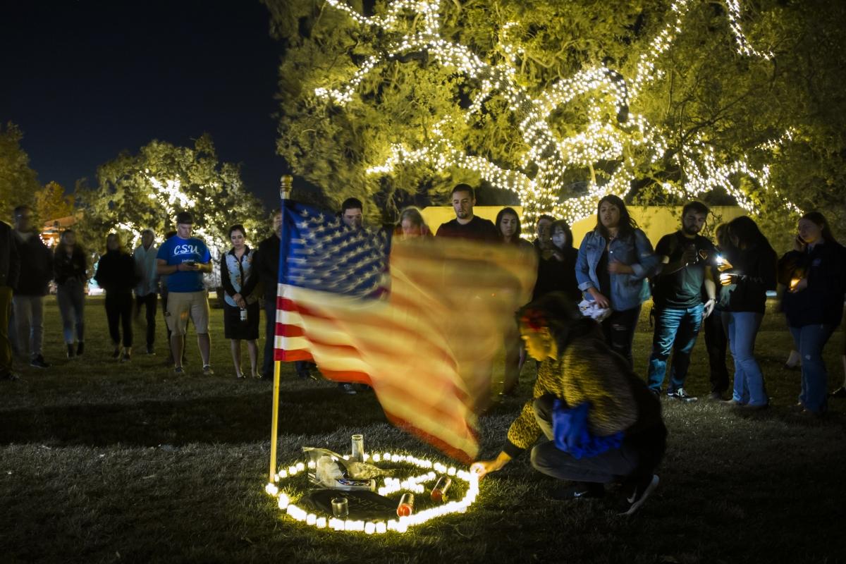 Gyászolók gyertyák és egy amerikai zászló körül Thousand Oaks városban  miután korábban egy férfi tüzet nyitott az ott zajló diákrendezvény résztvevőire. A lövöldözésnek legalább 13 halottja van(Photo by Apu Gomes / AFP)
