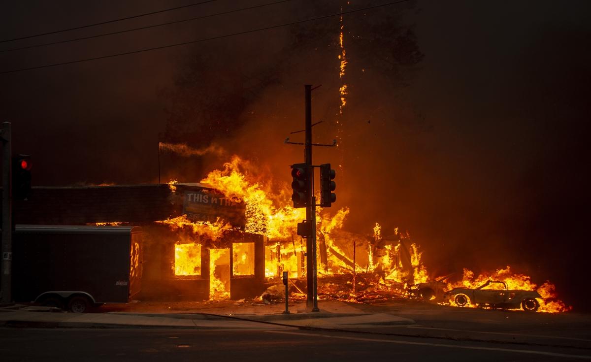 Lángok martalékává válik egy épület és egy autó a kaliforniai Buttle megyei Paradise közelében pusztító erdőtűzben 2018. november 8-án. Az alacsony páratartalom és az erős szél miatt gyorsan terjedő lángok miatt három északi megyében rendkívüli állapotot hirdettek és megkezdték a települések kiürítését. Paradise városban öt ember súlyosan megégett. (Photo by Josh Edelson / AFP)