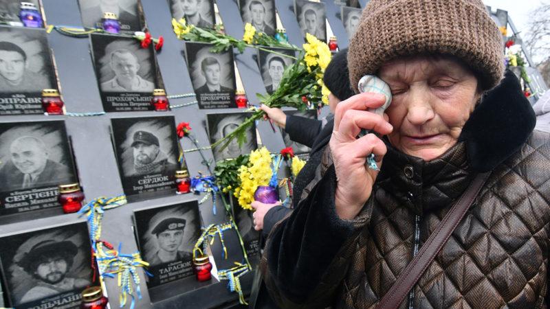 Virágot hagy egy ukrán nő a Majdan-tüntetések áldozatainak emlékfalánál Kijevben 2018. november 21-én. Öt évvel korábban ezen a napon kezdődtek az Euromajdan ellenzéki társulás erőszossá fajuló kormányellenes tiltakozásai Kijev főterén, a Majdanon. 2014. (Photo by Genya SAVILOV / AFP)