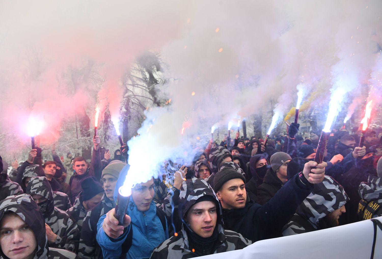 Az ukrán nacionalista Azov önkéntes zászlóalj politikai pártjának aktivistái tüntetnek a kijevi parlament előtt 2018. november 26-án, azt követően, hogy Petro Porosenko ukrán elnök az éjszaka folyamán 60 napos hadiállapot bevezetését javasolta a Kercsi-szorosnál történt orosz agresszió miatt.. (Photo by Sergei SUPINSKY / AFP)