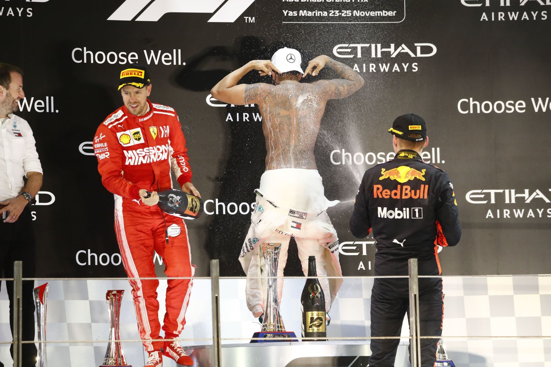A futamgyőztes Lewis Hamiltont, a Mercedes brit versenyzőjét locsolja pezsgővel a harmadik helyezett Max Verstappen, a Red Bull holland versenyzője a második Sebastian Vettel, a Ferrari német versenyzője mellett a Forma-1-es autós gyorsasági világbajnokság szezonzáró Abu-dzabi Nagydíjának eredményhirdetésén a Yas Marina versenypályán 2018. november 25-én. A 33 éves Hamilton megnyerte a 2018-as évadot, és ezzel az ötödik világbajnoki címét szerezte meg.