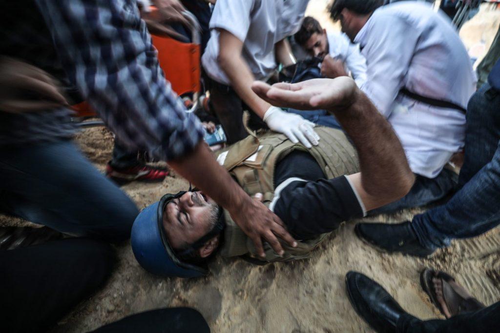 Palesztin tüntetők próbálnak segíteni Rasid Rasídnak, az Associated Press amerikai hírügynökség opeartőrének, akit meglőtt egy izraeli mesterövész a Gázai övezet északi, tengerparti határsávjánál 2018. november 19-én.Mustafa Hassona / Anadolu Agency
