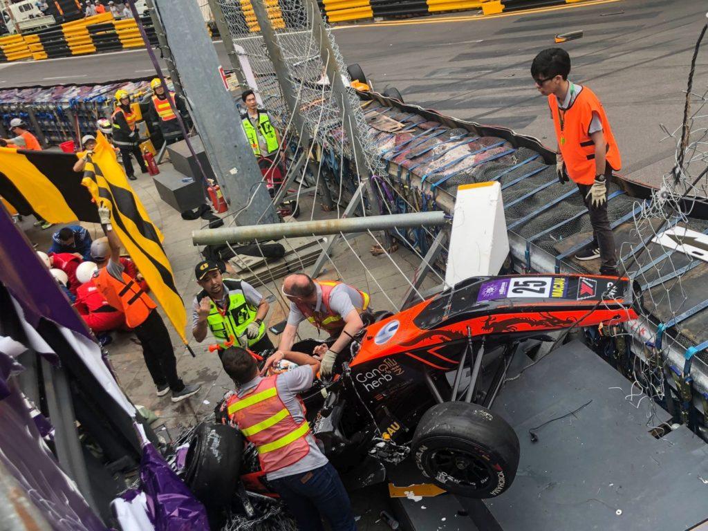 A 2018. november 18-i képen a német Sophia Flörsch autója átrepül a japán Cuboi So felett, miután több mint 250 kilométer óránkénti sebességnél ütközött egy riválisa autójával a Forma-3-as autós gyorsasági világbajnokság évzáró Makaói Nagydíján. A 17 éves versenyző kerítésnek csapódott, és eltört egy nyakcsigolyája, ezért másnap megoperálták egy makaói kórházban, amelyet még legalább egy hétig nem hagyhat el. A balesetben további négy ember sérült meg.(Photo by Christiaan Hart/Getty Images)