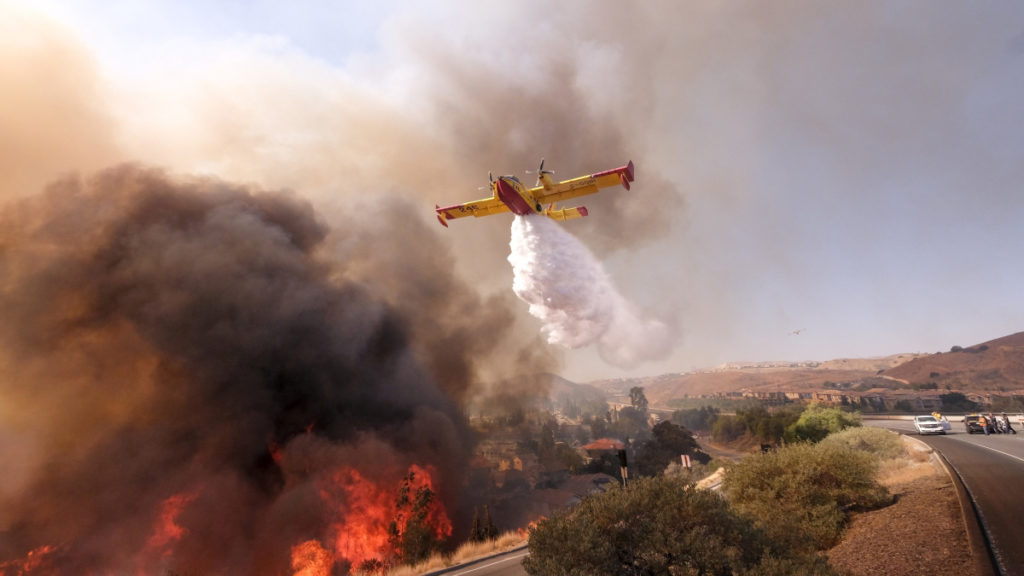Simi Valley, 2018. november 13.Repülőgépről ledobott tűzgátló anyaggal küzdenek a lángok megfékezésén a kaliforniai Simi Valley környékén pusztító erdőtűz helyszínén 2018. november 12-én. Az egy hete kitört kaliforniai tűzvész eddig legkevesebb 31 halálos áldozatot követelt, az eltűntek száma meghaladja a kétszázat.MTI/AP/Ringo H.W. Chiu