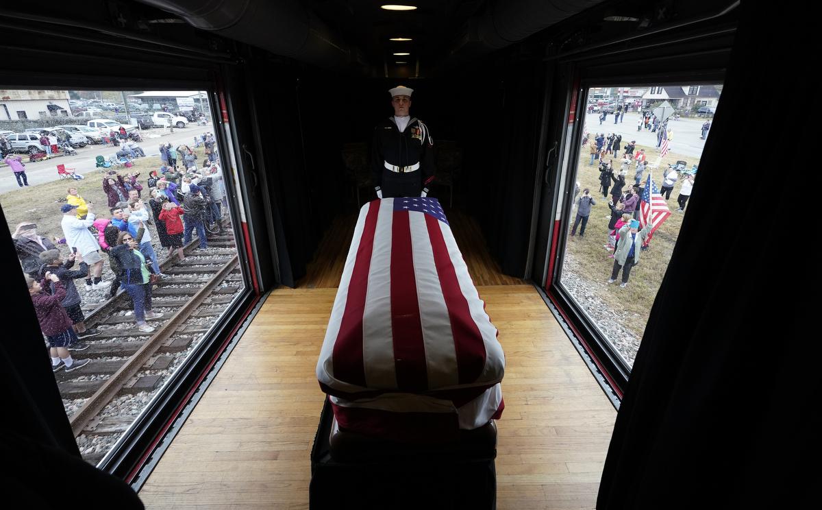 Gyászolók várják a George H. W. Bush korábbi amerikai elnök koporsóját szállító vonatot a Texas állambeli Millicanban. Az Egyesült Államok 41. elnökét, a 94 éves korában elhunyt George H. W. Busht a róla elnevezett elnöki könyvtár épületében helyezik örök nyugalomra a felesége és kislánya mellett a Houstontól északnyugatra fekvő College Station egyetemi kisvárosbanFotó:David J. Phillip / POOL / AFP
