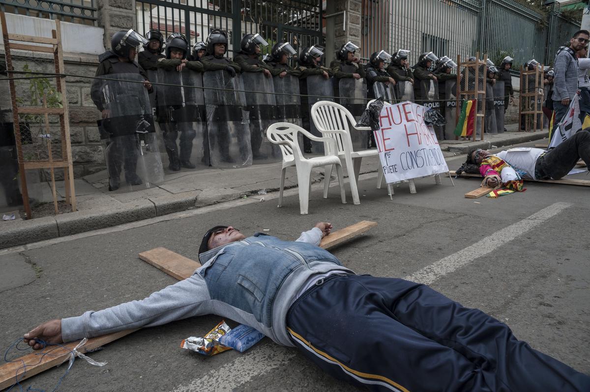llenzéki tüntetők fából ácsolt keresztekre feküdve tiltakoznak Evo Morales bolíviai államfő újbóli indulása ellen a legfőbb választási bíróság épületénél La Pazban. A testület az előző napon szabad utat engedett a 2006 óta hivatalban lévő államfőnek, hogy negyedszer is indulhasson a 2019 elején esedékes elnökválasztáson. Fotó: Marcelo Perez del Carpio/dpa/AFP