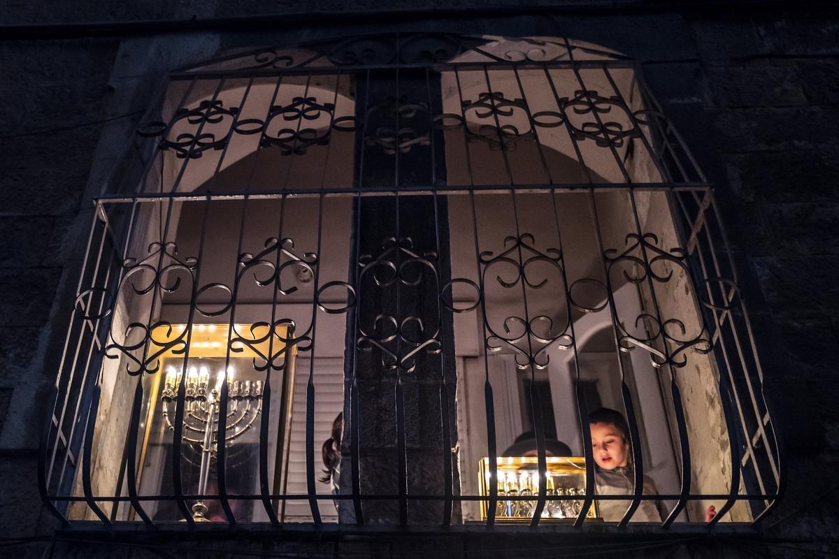 Ultraortodox zsidó kisfiú mécsest gyújt az otthonuk ablakában a nyolcnapos zsidó vallási fényünnep, a hanuka ötödik napján Jeruzsálemben.Fotó:Jim Hollander/EPA/MTI