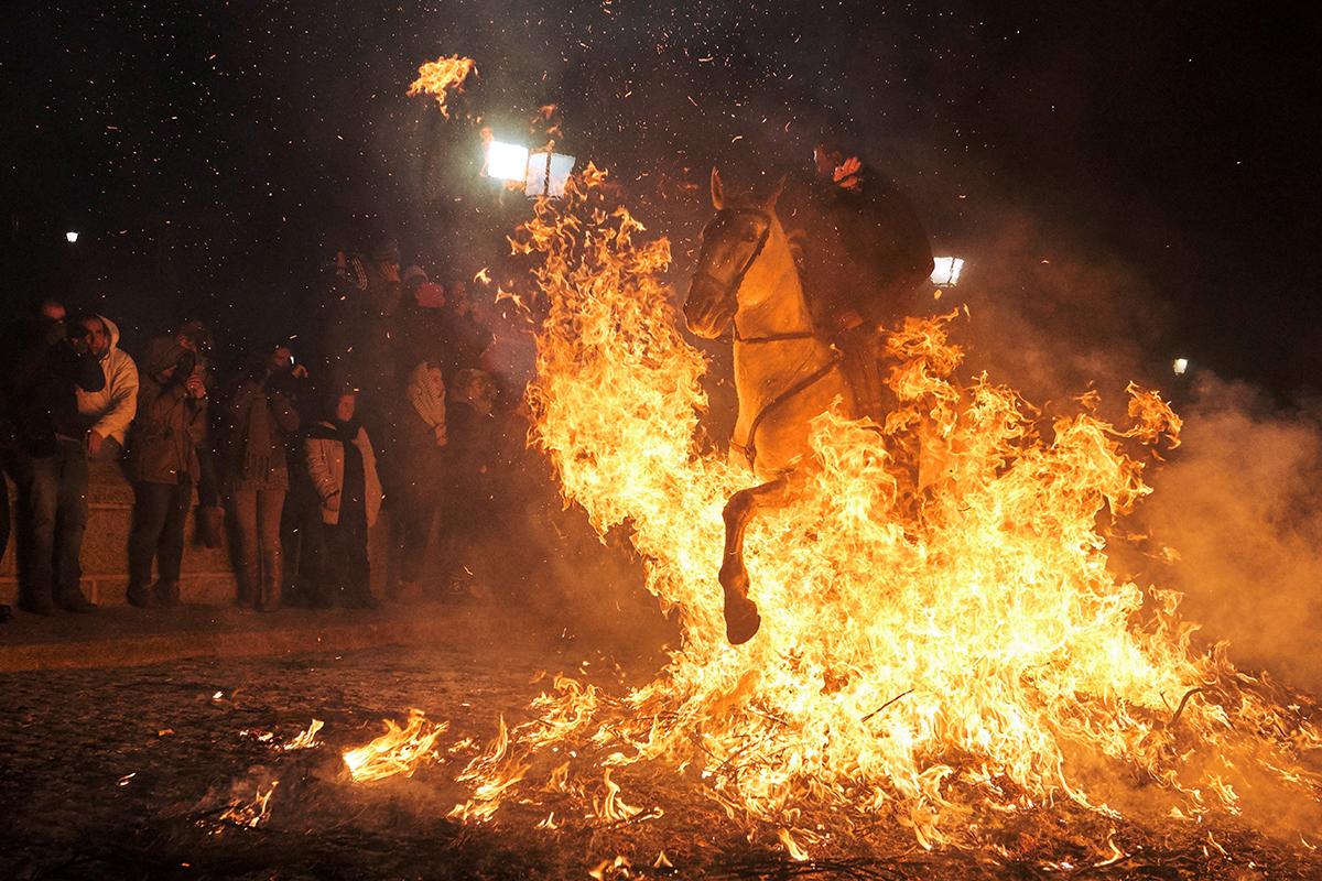 San Bartolomé de Pinares, 2019. január 17.Máglya lángján lovagol keresztül egy férfi San Bartolomé de Pinaresben 2019. január 16-án. A Madridtól mintegy 100 kilométerre nyugatra fekvő, közép-spanyolországi kis faluban hagyományosan tűzlovaglással és tűzugrással tisztelegnek Remete Szent Antalnak, a háziállatok védőszentjének emléke előtt a szent ünnepének előestéjén. Az 500 éves múltra visszatekintő ünnepségen több tucat lovas vesz részt, hogy a máglyatűz füstjével megtisztítsa és védelemmel lássa el állatát az előtte álló évre.MTI/EPA/EFE/Raúl Sanchidrián