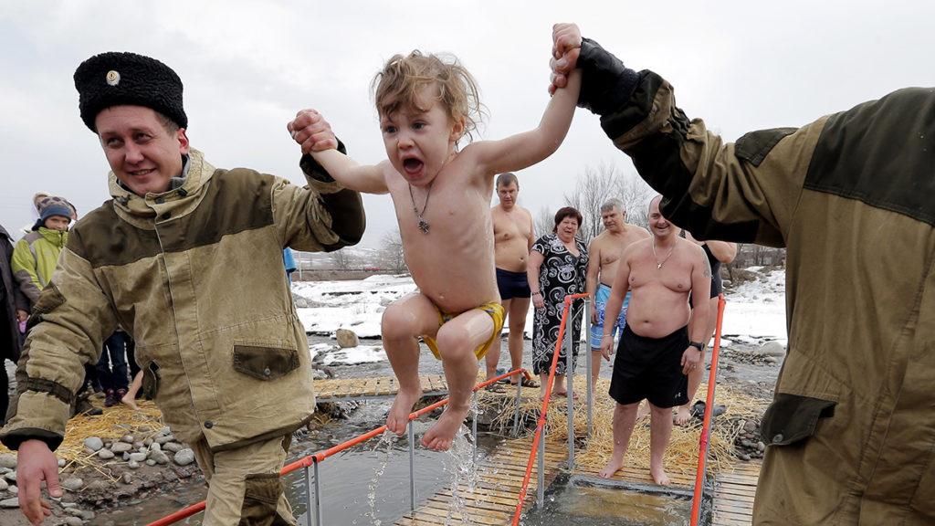 Voroncovka, 2019. január 20.Jeges tóvizbe mártanak egy kisgyereket a kirgiz főváros, Biskek közelében levő Voroncovka falu határában 2019. január 19-én, az ortodox vízkereszt ünnepén. Az ortodox hívők szerint a pópa által megszentelt jeges vízbe merülés erősíti a testet és megtisztítja a lelket az elkövetett bűnöktől.MTI/EPA/Igor Kovalenko