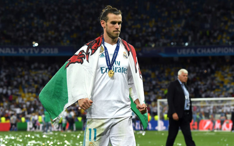 KIEV, UKRAINE - MAY 26: Gareth Bale of Real Madrid walks off the pitch with a Wales flag drapped over him after the UEFA Champions League Final between Real Madrid and Liverpool at NSC Olimpiyskiy Stadium on May 26, 2018 in Kiev, Ukraine.  (Photo by David Ramos/Getty Images)