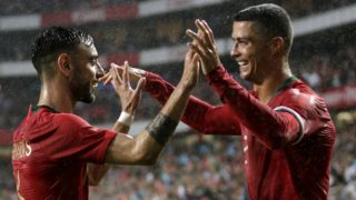 Portuguese defender Bruno Fernandes (L) celebrates with captain Cristiano Ronaldo after scoring a goal during the friendly football match between Portugal and Algeria, on June 7, 2018 at the Luz stadium  in Lisbon. / AFP PHOTO / JOSE MANUEL RIBEIRO