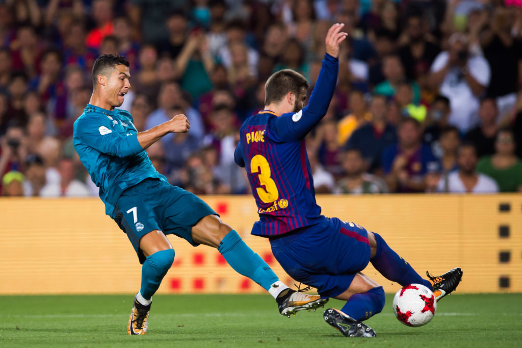 BARCELONA, SPAIN - AUGUST 13:  Cristiano Ronaldo of Real Madrid CF shoots the ball under pressure from Gerard Pique of FC Barcelona during the Supercopa de Espana Supercopa Final 1st Leg match between FC Barcelona and Real Madrid at Camp Nou on August 13, 2017 in Barcelona, Spain.  (Photo by Alex Caparros/Getty Images)