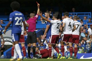 Chelsea's English defender Gary Cahill (C) is shown a red card by English referee Craig Pawson after a foul on Burnley's Belgian midfielder Steven Defour during the English Premier League football match between Chelsea and Burnley at Stamford Bridge in London on August 12, 2017. / AFP PHOTO / Ian KINGTON / RESTRICTED TO EDITORIAL USE. No use with unauthorized audio, video, data, fixture lists, club/league logos or 'live' services. Online in-match use limited to 75 images, no video emulation. No use in betting, games or single club/league/player publications.  /
