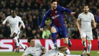 Chelsea's Spanish defender Cesar Azpilicueta (bottom) tackles Barcelona's Argentinian forward Lionel Messi during the UEFA Champions League round of sixteen second leg  football match between FC Barcelona and Chelsea FC at the Camp Nou stadium in Barcelona on March 14, 2018. / AFP PHOTO / Pau Barrena