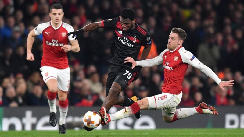 AC Milan's Ivory Coast midfielder Franck Kessié (L) vies with Arsenal's Welsh midfielder Aaron Ramsey during the UEFA Europa League round of 16 second-leg football match  between Arsenal and AC Milan at the Emirates Stadium in London on March 15, 2018.  / AFP PHOTO / Ben STANSALL